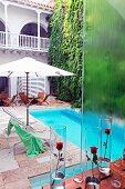 Rote Rosen in Glasvasen auf Tisch und Blick von oben auf Pool mit Liegestühlen unter Sonnenschirm im Innenhof eines Hotels im Kolonialstil