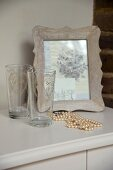 White pearl necklace, two glasses and picture in wooden frame on cabinet