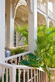 Elegant veranda with rounded arches attached to elegant, white, colonial-style building with palm trees