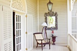 Antique armchair on white veranda; open lattice door with rounded arch above