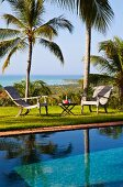 Holiday atmosphere - garden furniture and drinks on side table next to pool in garden of palm trees with sea view