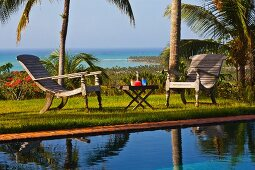 Relaxation area next to pool in garden of palm trees with sea view