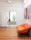 Orange sofa on wooden floor in foyer with open double doors and view into living room beyond