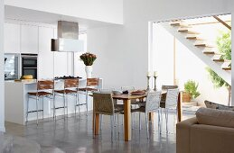 Dining area next to open-plan kitchen with floor-to-ceiling terrace window and view of external staircase