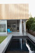 Contemporary house with open terrace door behind stone-edged pool
