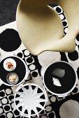 Designerstuhl und dekorierte Beistelltische auf Teppich mit schwarzweissem Kreismuster im 60er Jahre Retrostil