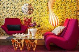 Gestreifte Designer-Lampe, Sessel und Glastisch vor gemusterter Tapete in Wohnzimmerecke