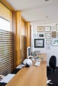 Picture gallery at the end of a writing desk in front of a wall of windows with built in blinds
