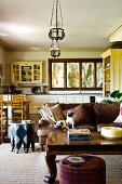 Heavy coffee table and sofa in country-style, open-plan interior with dining area in front of fitted kitchen