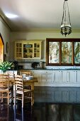 Country style: dining area on a high gloss, dark wooden flooring and kitchen counter with white, lower cabinets