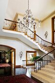 Spacious foyer with winding staircase and view of potted plant in hallway through arched doorway with wooden frame