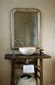 Rustic washstand with white basin and designer tap fitting below silver-framed mirror