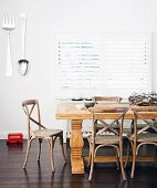 Dining area with solid wood dining table & oversized cutlery decorating wall