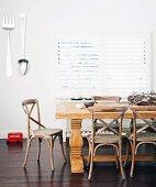 Esszimmerbereich mit Esstisch aus massivem Holz & übergrossem Besteck als Wanddeko
