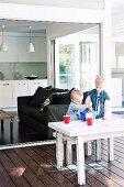 Kinder beim Backen an Tisch auf überdachter Veranda