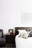 Dark wood bed & bedside cabinet in white bedroom
