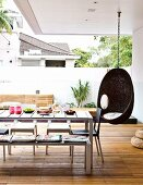 Hängestuhl & Tisch mit Stühlen und Sitzbank auf deckartiger überdachter Terrasse