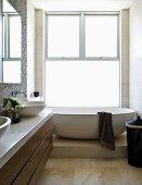 Bad mit Waschtisch & ovaler freistehender Badewanne auf Podest vor raumhohen Schiebefenstern