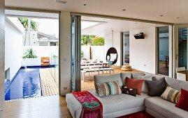 Wohnzimmer mit Eckcouch & geöffneten Falttüren zur deckartigen überdachten Terrasse mit Poolanlage