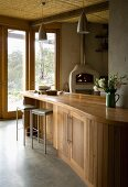 Curved, wooden kitchen counter and dainty bar stools in front of terrace doors with a view of the garden