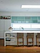 weiße Einbauküche mit modernen Fronten, ein Vintage Wandschrank und Korbstühlen an der Küchentheke