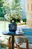 Weisser Blumenstrauss in blauer Porzellanvase auf rundem Beistelltisch vor Glasbrüstung