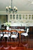 Essplatz im Antikstil mit langer Esstafel und romantischen Sitzkissen auf Holzstühlen in offenem Wohnraum mit gediegener Einbauküche