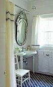 Opulenter Spiegel über Waschbecken in kleinem Bad mit schwarzweissen Bodenfliesen