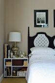 Nachttisch mit Büchern und eleganter Tischlampe neben dem schwarzweiss gestalteten Kopfteil eines Doppelbettes