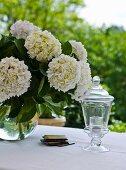 Hortensienstrauss und kelchförmiges Windlicht auf weiss gedecktem Tisch im Freien