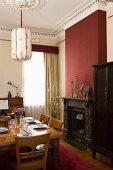 Gedeckter Esstisch vor offenem Kamin in bordeaux-farbener Wand in herrschaftlichem Esszimmer mit Stuckdecke