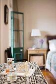 Parfumflakons und Schmuckkästchen auf gemustertem Deckchen im Schlafzimmer