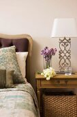 Holznachttisch und Tischleuchte mit weissem Lampenschirm und Metallfuss neben Bett mit gepolstertem Kopfteil