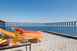 Refreshing drinks on side table and bright towels on sun loungers on roof terrace with sea view