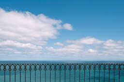 Oriental-style wrought iron balustrade in front of ocean panorama