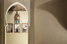 View of pendant lamp with metal lampshade and framed photographs through doorway with Oriental pointed arch