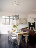 Wooden table and retro, wire mesh chairs below pendant lamp suspended from ceiling rose