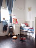Child's bedroom in white with storage baskets below bed and wooden royal guards on dark wooden floor