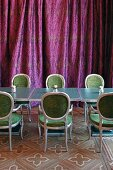 Kleine Tische mit Polsterstühlen vor violettem Vorhang im Speisesaal