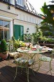 Filigrane Metall Stühle am gedeckten Nachmittagstisch auf Holzterrasse vor traditioneller Villa