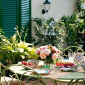 Kaffeeservice aus Keramik und blauem Muster und Gartenstrauss auf Tisch vor Wohnhaus mit geschlossenen, grünen Fensterläden