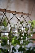 Decorative glass tealight holders hanging from metal rod