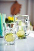 Zitronenwasser im Glas und in der Karaffe auf weißem Tisch