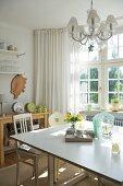 Sonnige, einfache Küche mit Erker, quadratischem Esstisch und Vintage Stühlen; über dem Tisch ein Kristallleuchter