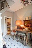 Rustikaler Tisch mit Hocker und Polstersessel im Treppenaufgang eines renoierten Landhauses