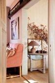Rustikaler Konsolentisch und lachsfarbenes Landhaussofa in zwei verschiedenen Räumen
