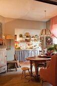 Landhausmix mit rustikalen Holzmöbeln und sanften Shabby Farben in Esszimmer mit Blick in die Küche