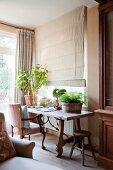 Antiker Polsterstuhl und rustikaler Holztisch mit Zimmerpflanzen vor einem Fenster mit geschlossenem Faltrollo