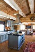 Landhausküche mit Mittelblock und hellgrau lackierten Holzfronten in offenem Wohnraum eines Blockhauses