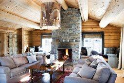 Gemütliche Sofagarnitur und Holz Couchtisch unter moderner Deckenleuchte mit Retro Touch im Wohnraum einer Blockhütte mit offenem Kamin